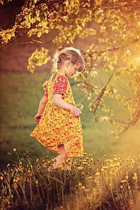 girl wearing yellow and red floral dress