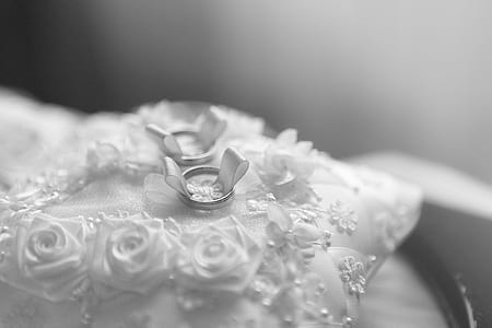 selective focus photo of silver-colored bridal ring on white lace pillow