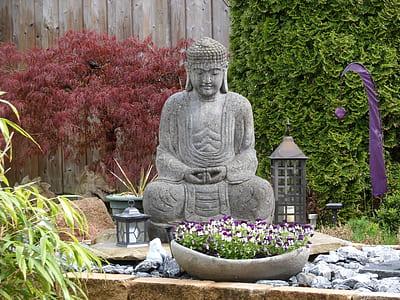Gautama Buddha statue surrounded of plants