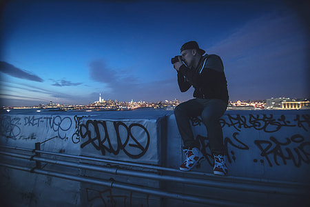 A man takes a photo at night in New York