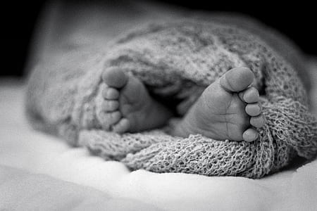 Greyscale Photo Of Human Feet Covered In Knitted Comforter