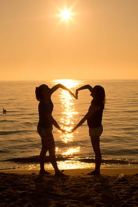 silhouette of two women forming heart during golden hour