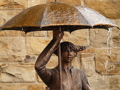 man holding umbrella statuette