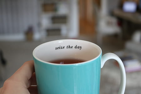 person holding white and teal ceramic mug