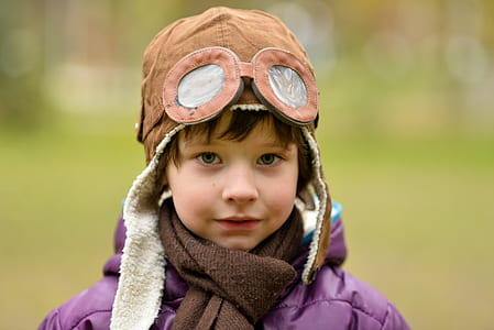 close-up photography of toddler wearing brown aviator cap and brown scarf