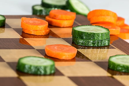 sliced cucumber and carrots on brown chess board
