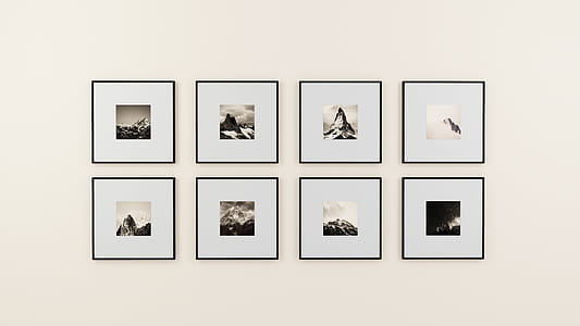 eight square black wooden photo frames on white painted wall