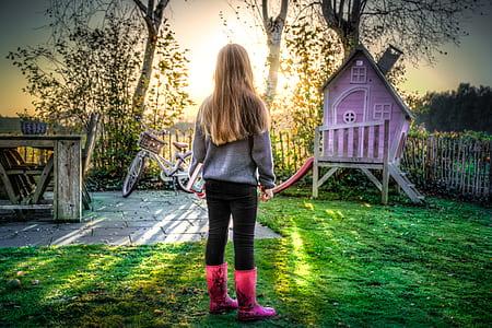 closeup photo of girl in backyard facing towards the sun rays