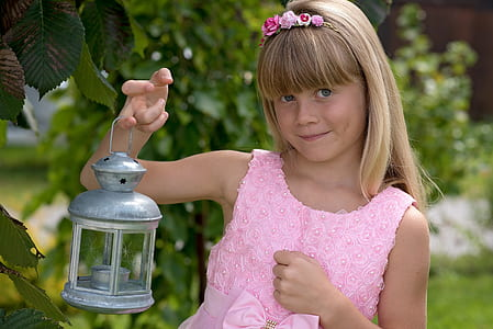 girl with pink floral scoop-neck sleeveless shirt holding camping lantern