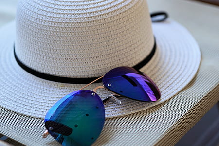purple sunglasses beside white strawhat