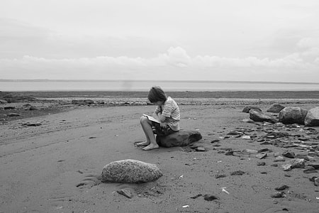 boy seating on rock at beach shore black and white photo