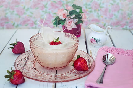 pink bowl filled with white cream and strawberry