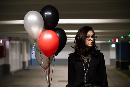 woman wearing eyeglasses and black top holding balloons on parking lot