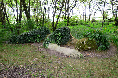 landscape photograph of reclining woman soil sculpture with green plants