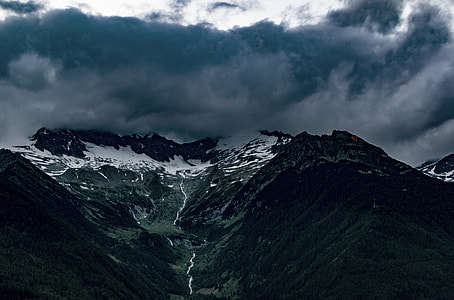green mountain under blue and white clouds during daytime