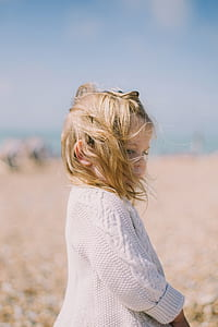 toddler girl wearing white long-sleeved shirt with blonde hair during daytime