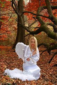 blonde-hair woman in angel dress near tree