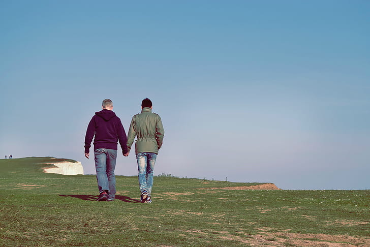 two people walking on green grass field under blue sky