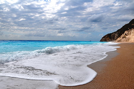 landscape photography of beach under cloudy sky during daytime