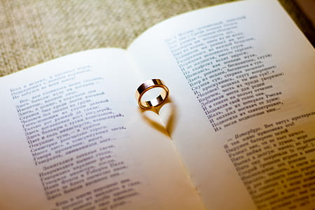 gold-colored wedding band on white book page