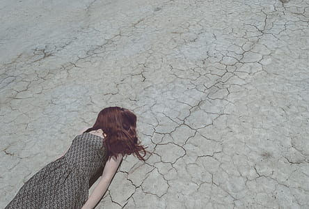 woman wearing gray sleeveless dress lying on ground during daytime