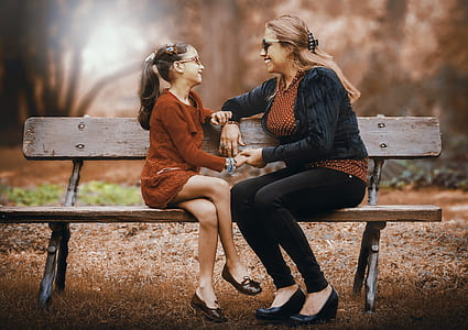 mother and daughter sitting on the bench