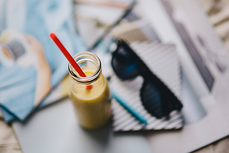 Healthy shake in a small bottle with a straw and sunglasses