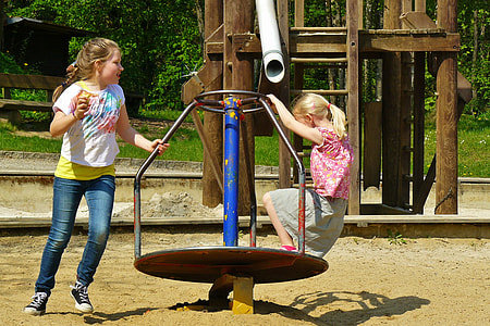 two girl playing on playground Mary-go-round during daytime