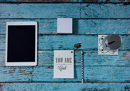 iPad beside notebook, pencil, sticky note pad, and mason jar