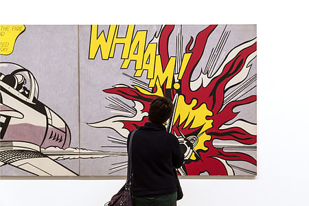 A person looks at pop art by Roy Lichtenstein in an art gallery in London, England