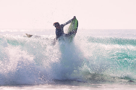 man riding surf board at day time