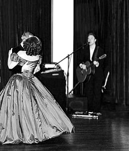 grayscale photo of man playing guitar while singing and man dancing with woman on floor