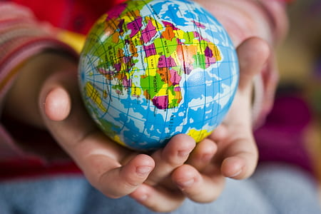 person holding blue terrestrial globe
