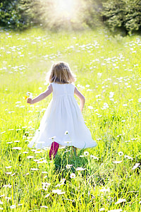 girl running in flower field during daytime