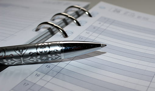 silver ballpoint pen on top of book