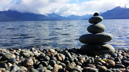 closeup photo of balance stones near body of water