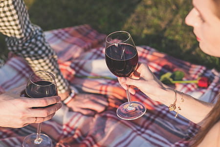 two people holding clear wine glasses during daytime