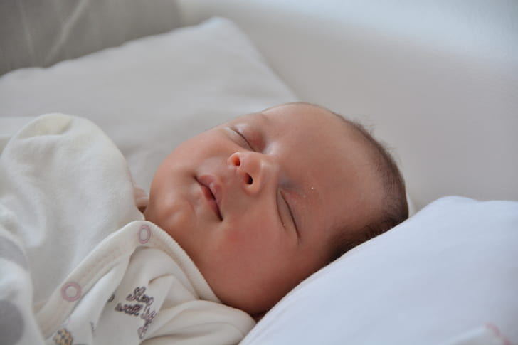 sleeping baby laying on white pillow