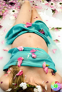 woman in water filled with flower petals