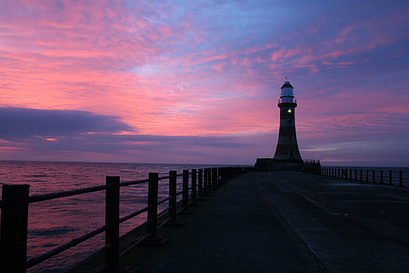 silhouette of lighthouse on wooden dock under pink and blue sky