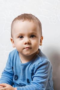 boy wearing blue crew-neck long-sleeved shirt