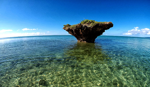 brown stone formation in the middle of body of water