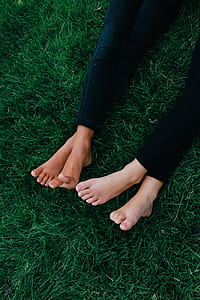two person lying on green lawn grass wearing black denim jeans