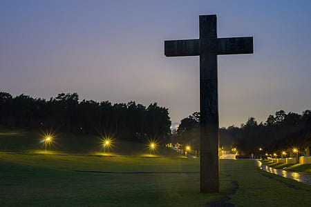Brown Cross Statue on Green Grass Field With Turned on Light during Nighttime