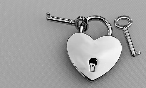 silver-colored heart padlock with key