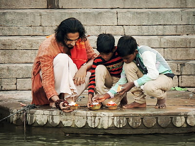 man and two boys sitting holding candles beside body of water