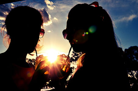 silhouette of two women zipping drinks during golden hours