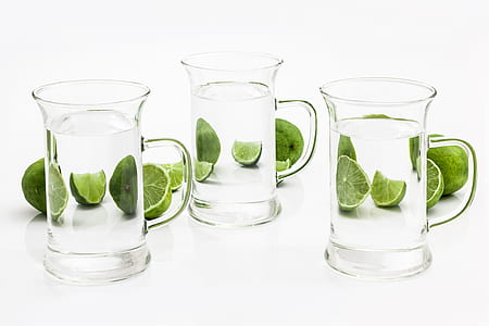 three clear glass mugs and slice lime fruit