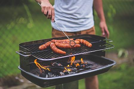man grilling food during daytime