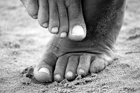 grayscale photograph of person's foot stepping on sand
